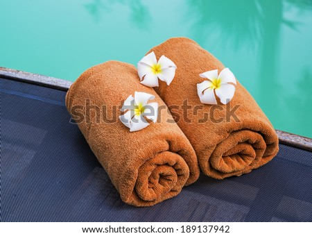 Rolled towels near the swimming pool  - stock photo