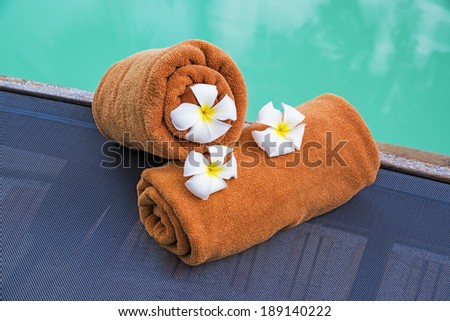 Rolled towels on pool chairs near swimming pool  - stock photo