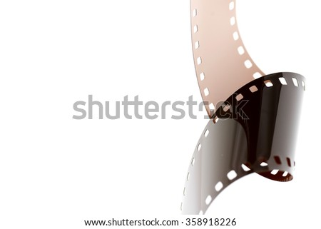 Rolled undeveloped film strip with copy space. - stock photo