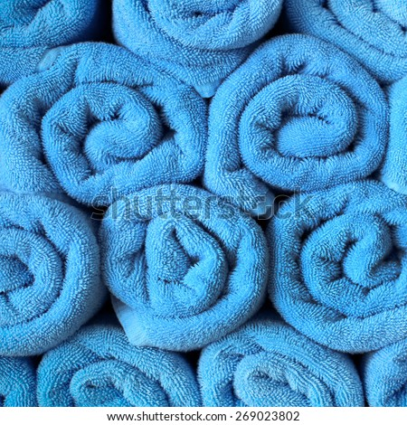 Rolled up blue spa towels in stack - stock photo