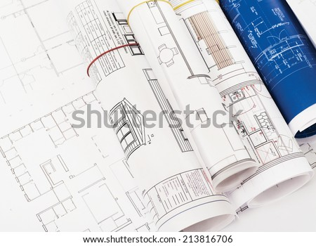 Rolled-up blueprints and house plans with copyspace - stock photo