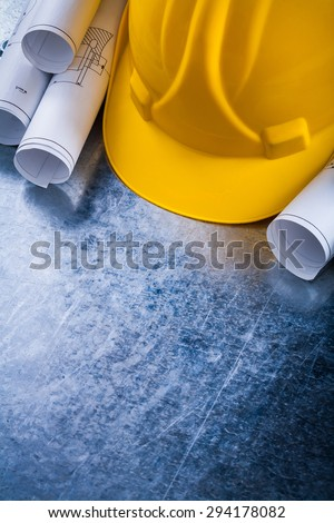 Rolled up construction plans and safety hard hat on metallic background building and architecture concept. - stock photo
