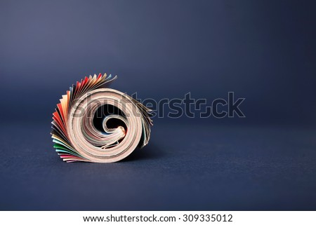 Rolled up magazine isolated on blue background - stock photo
