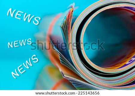 Rolled up magazines on blue background - stock photo