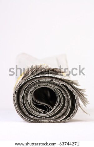 Rolled up newspaper on plain background with copy space - stock photo