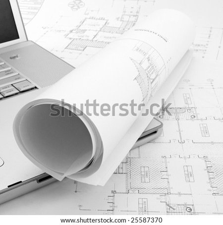 rolled up plans and laptop - stock photo