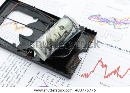 Rolled up scroll of US 100 dollar bill with portrait / image of Benjamin Franklin as a bait on black rat trap. A concept of difficulty in daily living which full of deception and need to be cautious. - stock photo