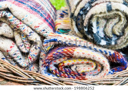 Rolled up wool blankets in a basket - stock photo