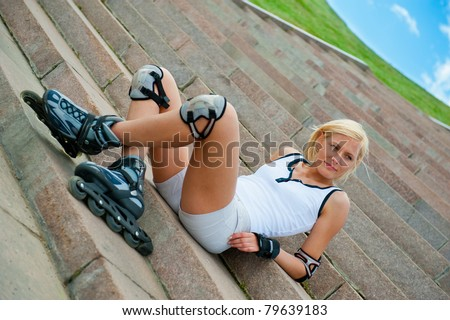 Roller blonde girl resting on the steps - stock photo