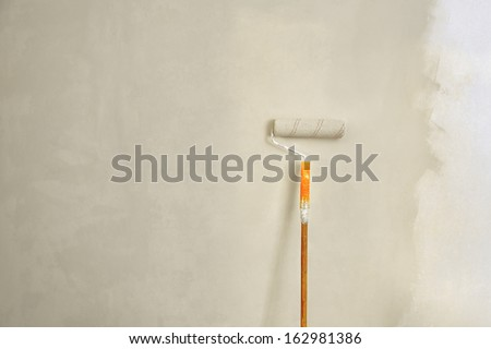 Roller brush with orange grip against wall. - stock photo