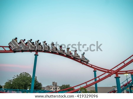 Roller coaster ride, intimating the height and speed and craze of fun and sacredness. Fast moving shoot of people. - stock photo
