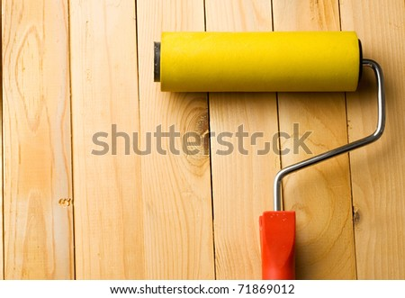 Roller isolated on wooden background - stock photo