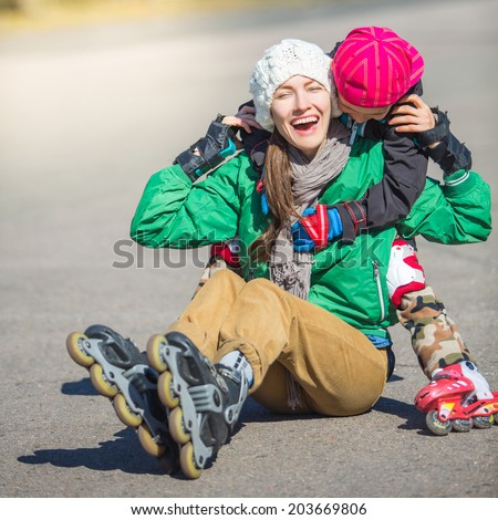 Roller skating -mother with son on roller skates, active family concept. focus on mother. daylight - stock photo