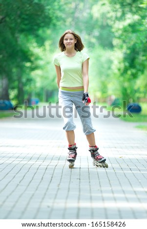 Roller skating sporty girl in park rollerblading on inline skates.  Caucasian woman in outdoor fitness activities.  - stock photo
