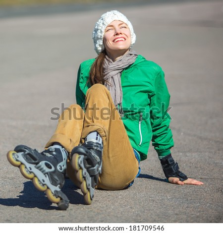 Roller skating sporty girl in park rollerblading on inline skates on a sunny spring day - stock photo