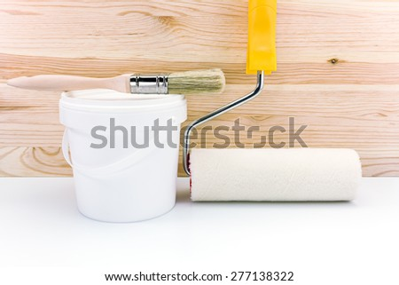 roller with brush and paint can against wooden boards - stock photo