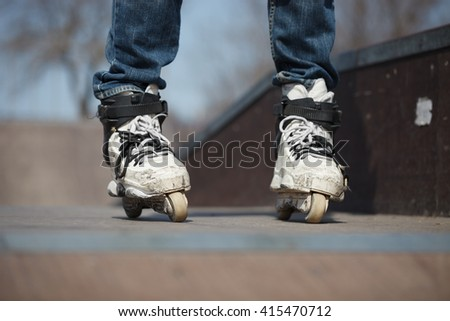 Rollerblader in skatepark wearing professional extreme inline skates made for tricks - grinding and jumping. Dangerous sport popular among youth and teenagers.  - stock photo