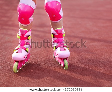 Rollerblades inline skates of a child closeup in action outdoors in sunny day  - stock photo