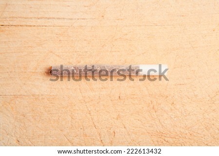 Rolling cigarette. Wood Background. - stock photo