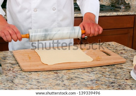 Rolling dough making beef wellington - stock photo