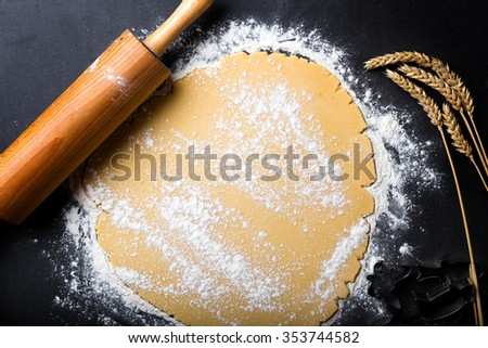 Rolling dough with wooden roller and flour on the black background