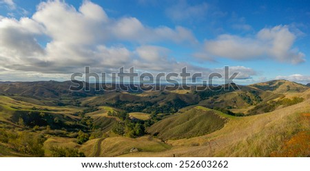 Rolling green hills lead to the Pacific Ocean in the distance of central California. - stock photo