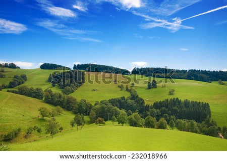 Rolling green hills of Germany with blue sky - stock photo