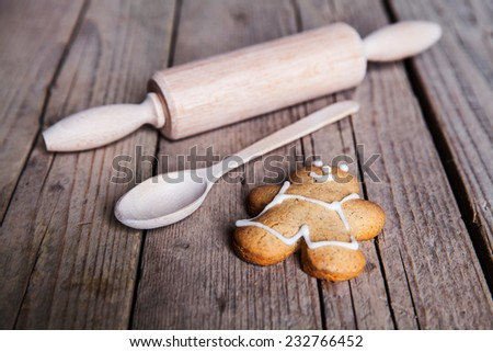 Rolling pin and homemade gingerbread men biscuits on a wooden board with flour