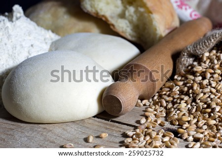 Rolling Pin with Dough and Wheat on Wooden Table Closeup - stock photo