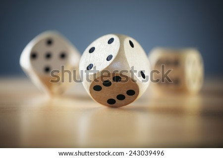 Rolling three dice on a wooden desk - stock photo