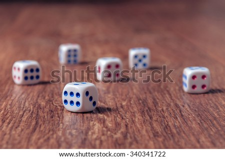 Rolling three dice on a wooden desk.