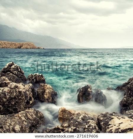 rolling wave slamming on the rocks of the coastline - stock photo