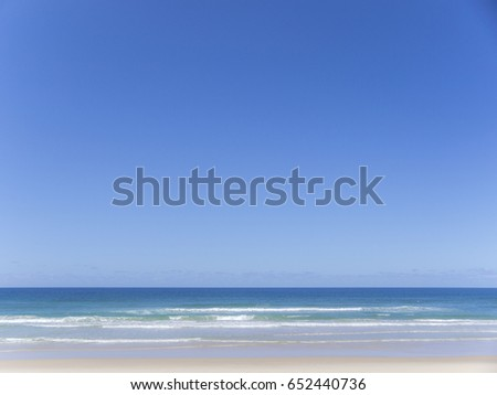 Rolling waves in a blue ocean under a blue sky on a beach near the Gold Coast, Queensland, Australia