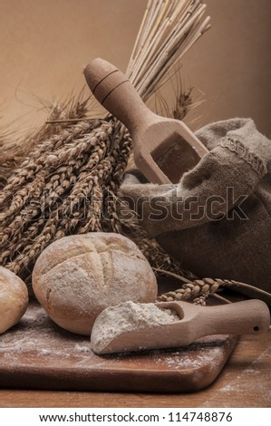 Rolls, bread and flour on wooden table