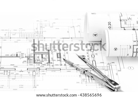 rolls of architectural blueprints and house plan with drawing compass - stock photo