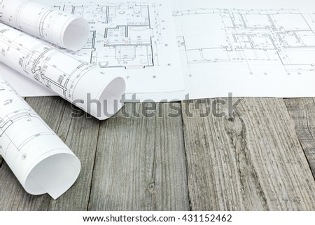rolls of architectural blueprints and technical drawings on gray wooden planks - stock photo
