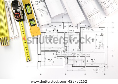 rolls of architectural blueprints and technical drawings with pencil, tape measure and spirit level - stock photo