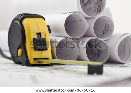 rolls of architectural house plans & tape measure - stock photo