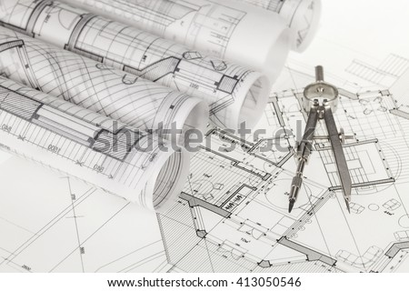 rolls of architecture blueprints, house plans &  compass - stock photo