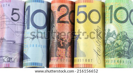 Rolls of Australian cash money with five, ten, twenty, fifty and one hundred dollar notes. - stock photo