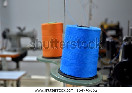 Rolls of blue and orange  yarn on sewing machines - stock photo