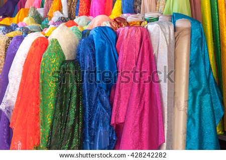 Rolls of brightly coloured fabrics and cloths
