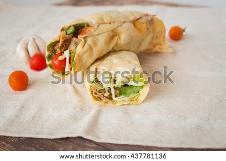 rolls of chicken kebab on wooden table