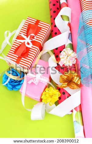 Rolls of Christmas wrapping paper with ribbons, bows on color background - stock photo