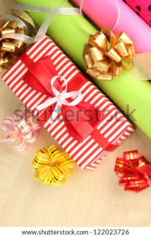 Rolls of Christmas wrapping paper with ribbons, bows on wooden background - stock photo