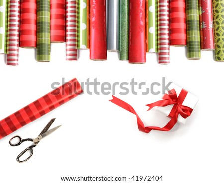 Rolls of colored wrapping  paper with scissors and gift on white background - stock photo