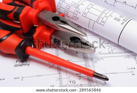 Rolls of electrical diagrams with work tools lying on construction drawing of house, drawings for the projects engineer jobs