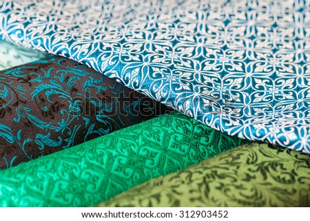 Rolls of fabric and textiles in a factory shop. Multi different colors and patterns on the market - stock photo