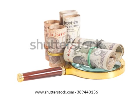 Rolls of Indian Currency Rupee Notes with magnifying glass on white background - stock photo