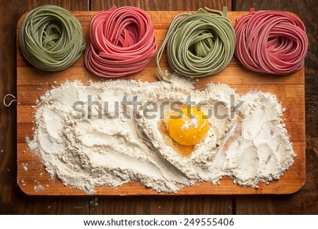 Rolls of multicolored pasta and heart made of flour and egg yolk - stock photo